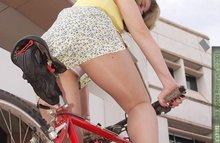 Дама катается на велосипеде и светит трусики