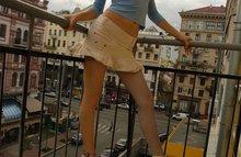Рыжая модель позирует на открытом балконе