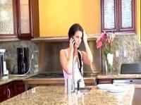 Девушка общается по телефону на кухне