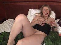 Зрелая сучка трахает себя фаллосом на кровати
