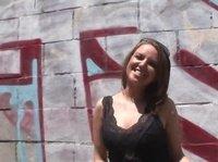 Неопытная красотка позирует около стены