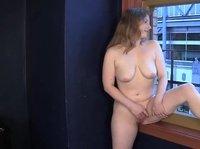 Пухленькая дамочка с большой грудью мастурбирует на подоконнике