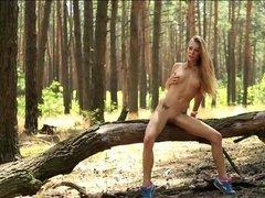 Молодая красотка гуляет обнаженной по лесу