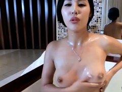 Красивая азиатка тщательно моет сексуальное тело в ванной